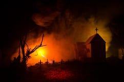 Страшный взгляд зомби на дереве кладбища мертвом, луне, церков и пугающем облачном небе с туманом, концепцией хеллоуина ужаса Стоковые Фото
