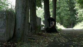 Страдая оплакивая женщина в похоронном платье на ее коленях на могиле ее мертвых любимых сожалений и скорбы чувства акции видеоматериалы