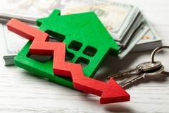 Стрелка вниз и дом с деньгами на белой деревянной предпосылке Понижаясь рыночная цена недвижимости стоковые фото