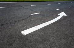 Стрелка знака уличного движения белая на дороге Стоковые Фото