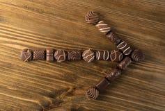 Стрелка помадок шоколада на старой деревянной предпосылке стоковое изображение rf
