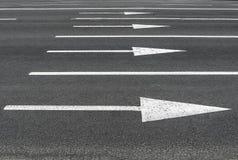 Стрелки дорожных разметок на черном асфальте стоковая фотография rf