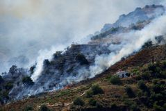 Стреловидность пламен лесного пожара к испанскому свойству между Sayalonga и аренами, Андалусией Стоковое фото RF