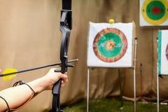 Стрелок в черточке подготавливает для съемки и направляет снять смычок в цели Стоковая Фотография RF
