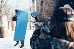 Стрельба игрока пейнтбола на враге с экраном Стоковая Фотография
