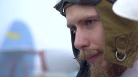 Стрельба конца-вверх бородатой пилотной стороны ` s в шлеме на фоне самолета сток-видео