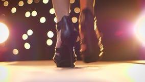 Стрельба конца-вверх обуви в светах, высокой пятки женщины, идя от камеры на накаляя предпосылке внутри помещения видеоматериал