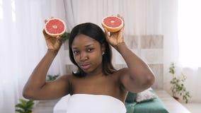 Стрельба очаровывать молодую африканскую женщину держа куски грейпфрута перед ее стороной пока представляющ для камеры видеоматериал