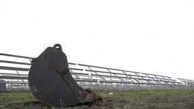 Стрельба слайдера ведра от бульдозера на фоне корпусов для панелей солнечных батарей видеоматериал