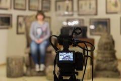 Стрельба ТВ на музее Монитор LCD на камкордере Девушка перед камерой Показатель интервью Стоковое Изображение