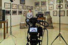 Стрельба ТВ на музее Монитор LCD на камкордере Девушка перед камерой Показатель интервью Стоковое Фото