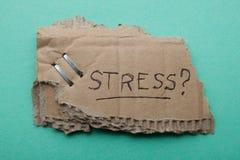 """Стрессы знака """"на сорванном картоне, зеленой предпосылке стоковая фотография"""
