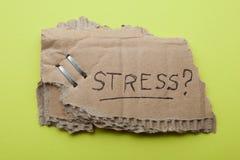 """Стрессы слова """"на старой части картонной коробки на яркой ой-зелен предпосылке стоковые фото"""
