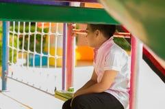 Стресс и одиночество азиатских мальчиков в спортивной площадке школы Стоковая Фотография RF