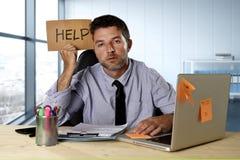 Стресс страдания бизнесмена работая на столе компьютера держа знак прося помощь смотря утомленное вымотанный