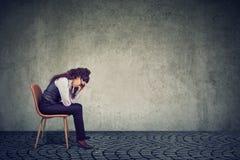 Стресс чувства женщины от работы сидя на стуле и смотря вниз стоковое фото