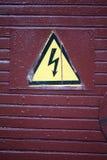 Стрелка знака опасности высоковольтная на пакостной деревянной двери Стоковое Фото