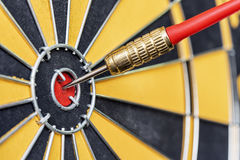 Стрелка дротика крупного плана красная ударяя в яблочке цели dartboard Стоковая Фотография