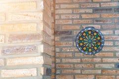 Стрелка дротика пропуская центр цели Dartboard на кирпичной стене Стоковые Фотографии RF