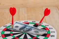 Стрелка дротика ударяя на dartboard с деньгами Стоковая Фотография