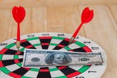 Стрелка дротика ударяя на dartboard с деньгами Стоковое Изображение