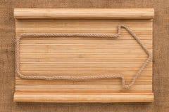 Стрелка сделанная веревочки лежа на бамбуковой циновке в форме рукописи Стоковая Фотография RF