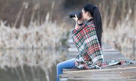 Стрельба девушки с камерой фото на реке Стоковое Изображение