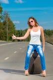 Стрельба девушки с чемоданом на дороге Стоковое Изображение