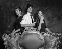 Стрельба детективного рассказа в студии женщины человека 2 агент 007 Человек в шляпе с пистолетом и 2 женщинами в черноте Стоковое фото RF