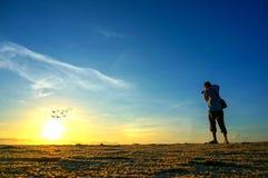 Стрельба фотографа около пляжа когда поднимать солнца Стоковые Фотографии RF