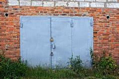 Стробы серого утюга на кирпичной стене перерастанной с зеленой вегетацией Стоковое Изображение
