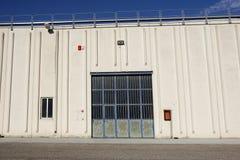 Строб груза промышленного склада дверь промышленная Взгляд на одном стробирует большого фасада склада Вид спереди Стоковая Фотография