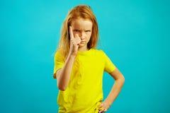 Строгая девушка ребенка 10 лет угрожает к пальцу на камере, имеет сердитый взгляд, демонстрирует настроение плена и зла стоковое фото rf