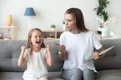 Строгая мама браня больн-поступаемую дочь кричащую громко дома стоковое фото