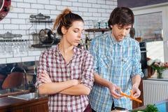 Строгая несчастная женщина варя с ее супругом на кухне Стоковая Фотография
