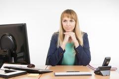 Строгий офис специалист сидя на столе и смотря посетителя Стоковые Изображения RF