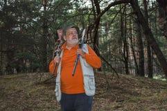 Строгий старший ренджер при 2 винтовки стоя в темном сосновом лесе Стоковые Изображения