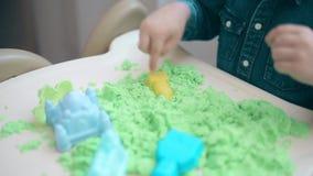 Строения ребенка с его руками от зеленых кинетических замков и башен песка акции видеоматериалы