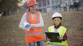 строители немногая 2 шлемы и жилета ребенка защитных изучают техническую документацию акции видеоматериалы