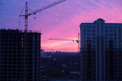 Строительная площадка жилого дома и crans в городе в восходе солнца стоковая фотография rf