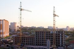 Строительная площадка и краны жилого дома в городе в восходе солнца стоковые фотографии rf