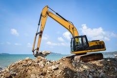 Строительная площадка камня экскаватора землекопа затяжелителя Backhoe работая на океане моря пляжа стоковое изображение