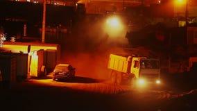 Строительная площадка на ноче, грузовики тележек управляет внутри вне, желтый видеоматериал