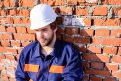 Строительная площадка шлема построителя сидит расслабляющая постная кирпичная стена Построитель защитного шлема Гая бородатый кра стоковые изображения rf