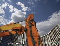 Строительная техника строительной техники, высоких и тяжелых на фоне здания под конструкцией Стоковое Фото