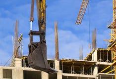 Строительная техника строительной техники, высоких и тяжелых на фоне здания под конструкцией Стоковые Изображения