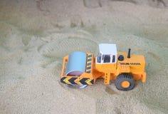 Строительное оборудование ролика дороги игрушки автомобиля на предпосылке песка Стоковое фото RF