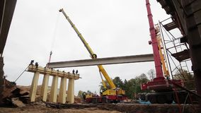 Строительство моста, работники в работе шлема, конкретный луч двинуто кранами видеоматериал