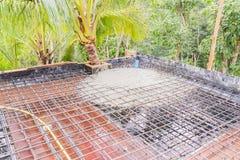 Строительная площадка: Бетон от ведра нагрузил для того чтобы настелить крышу форма-опалубка сляба и бар подкрепления Стоковые Фото
