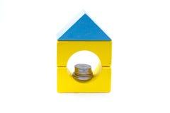 Строительные блоки с монетками внутри отверстия. Стоковое Фото
